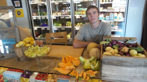 Sean offers samples of lemon cucs and melons at Country Organics